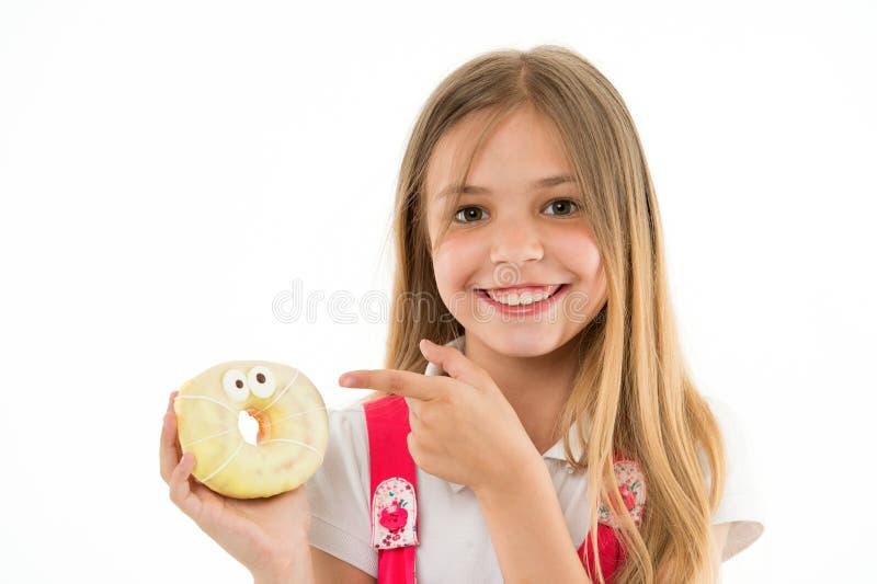 Het meisje op het glimlachen gezicht houdt zoete doughnut in hand, geïsoleerd op witte achtergrond Het jong geitjemeisje met lang royalty-vrije stock fotografie