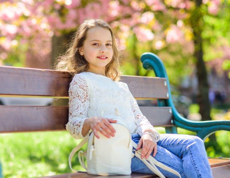 Het meisje op het glimlachen gezicht zit op bank, sakuraboom op achtergrond, defocused Toebehorenconcept Leuk kind met rugzak royalty-vrije stock afbeelding