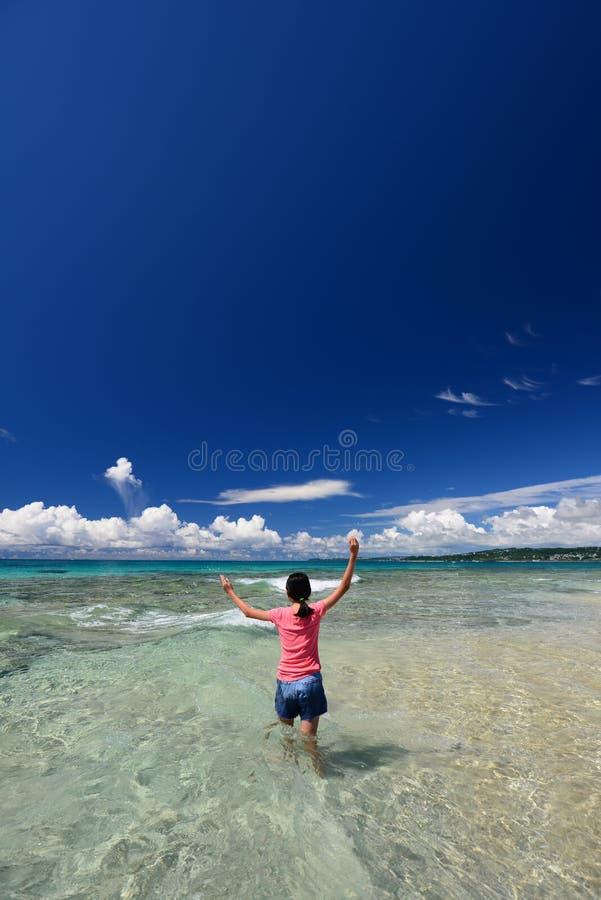 Het meisje op het strand geniet van zonlicht stock afbeeldingen