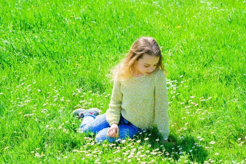 Het meisje op kalm of droevig gezicht besteedt in openlucht vrije tijd Het meisje zit op gras bij grassplot, groene achtergrond H royalty-vrije stock fotografie