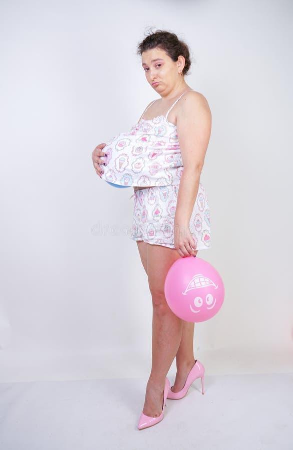 Het meisje op middelbare leeftijd wil werkelijk zwanger worden vrouw die zich in pyjama's met een luchtballon onder een t-shirt o royalty-vrije stock afbeeldingen