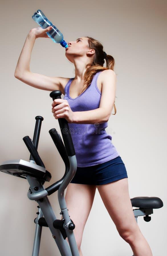 Het meisje op opleidingsapparaten drinkt water stock foto's