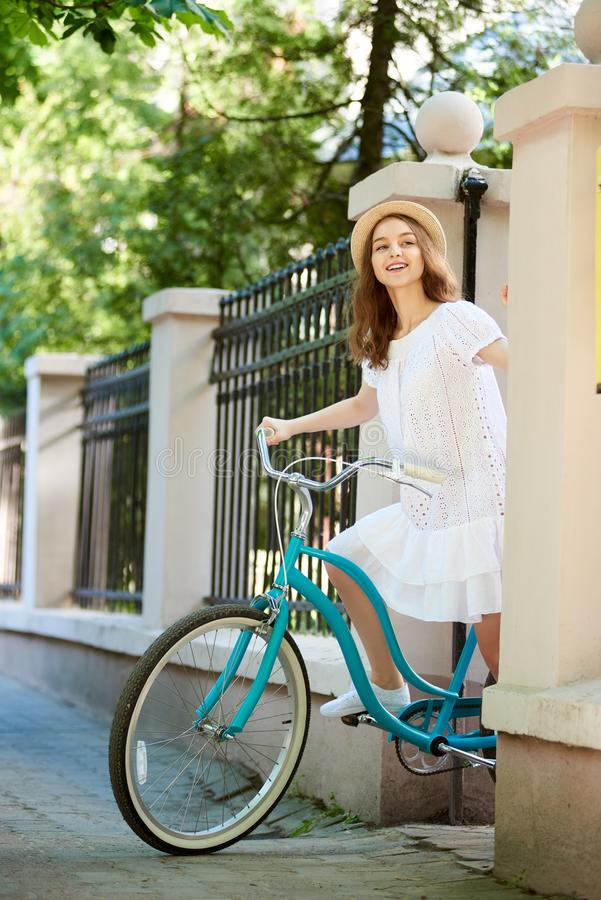 Het meisje op retro fiets gluurt uit van achter oude omheining stock afbeeldingen