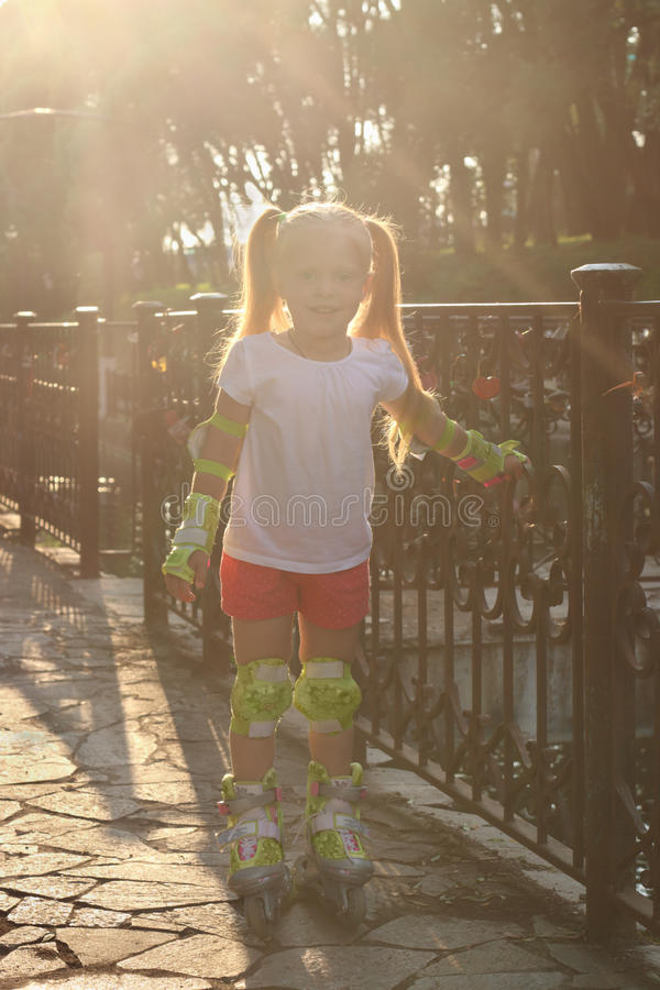 Het meisje op rolschaatsen stelt dichtbij traliewerk in zonnige su stock afbeeldingen
