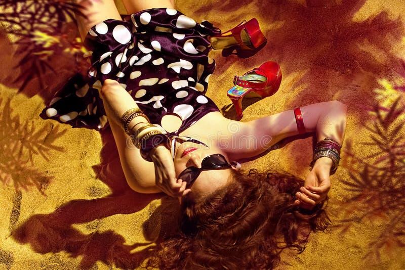 Het meisje op het strand ligt op het zand in de kleding stock afbeelding