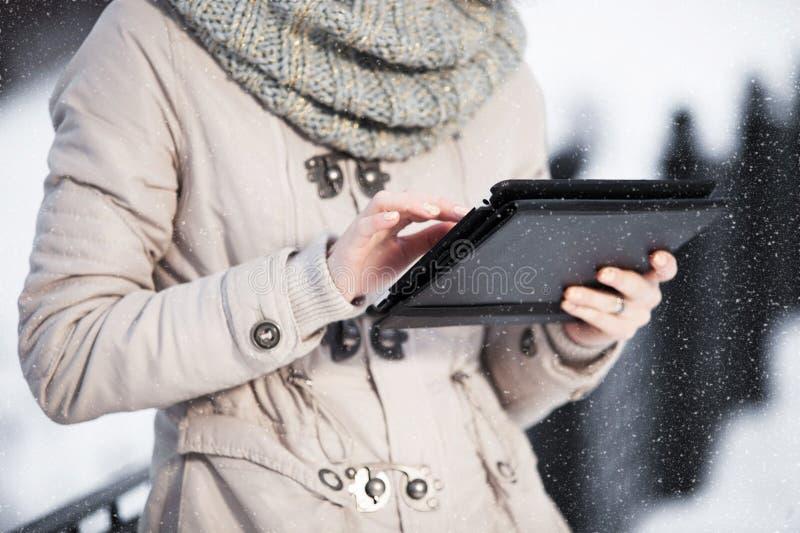 Het meisje op tabletsmartphone in de winterpark stock fotografie