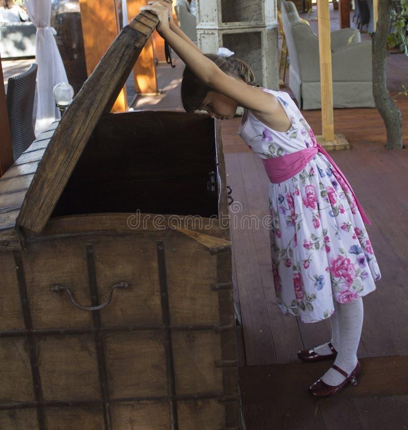 Het meisje op zoek naar schatten kijkt in een borst stock afbeeldingen