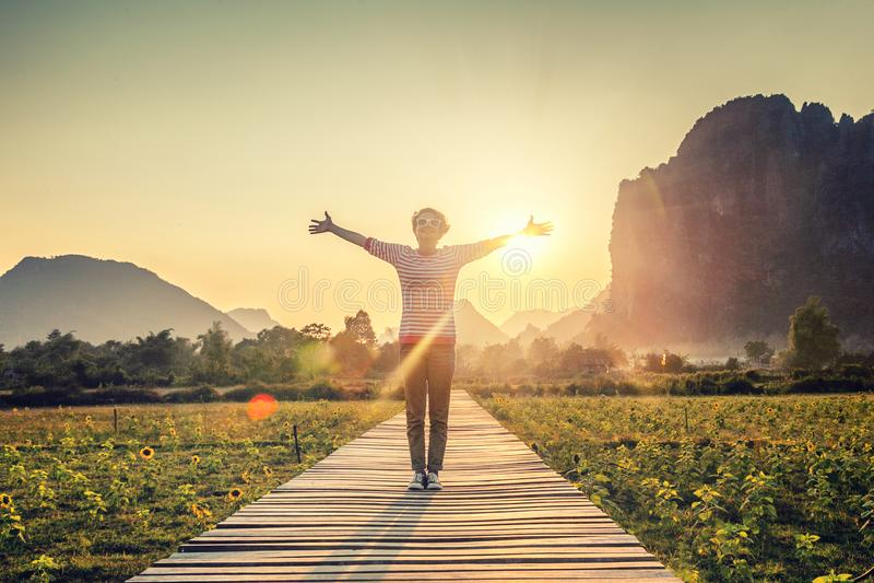 Het meisje op zonsondergangachtergrond, dient hand, vrijheid, geluk, pe in royalty-vrije stock fotografie