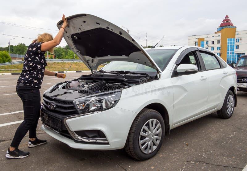 Het meisje opent de kap van een nieuwe auto Lada Vesta royalty-vrije stock afbeeldingen