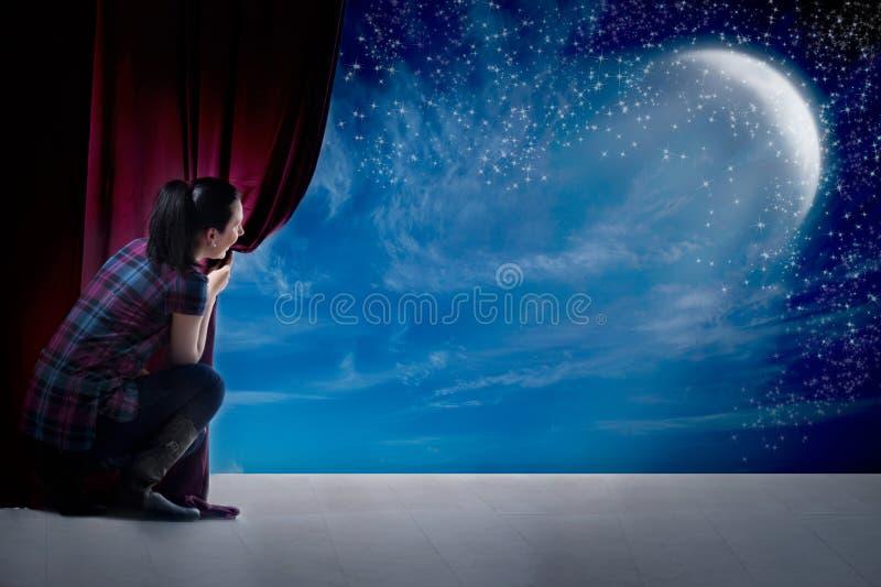 Het meisje opent het gordijn en de ingang in de magische wereld van maan stock afbeelding