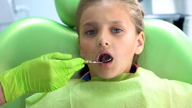 Het meisje opent mond voor tandarts om tanden met mondspiegel, routinecontrole te controleren stock foto
