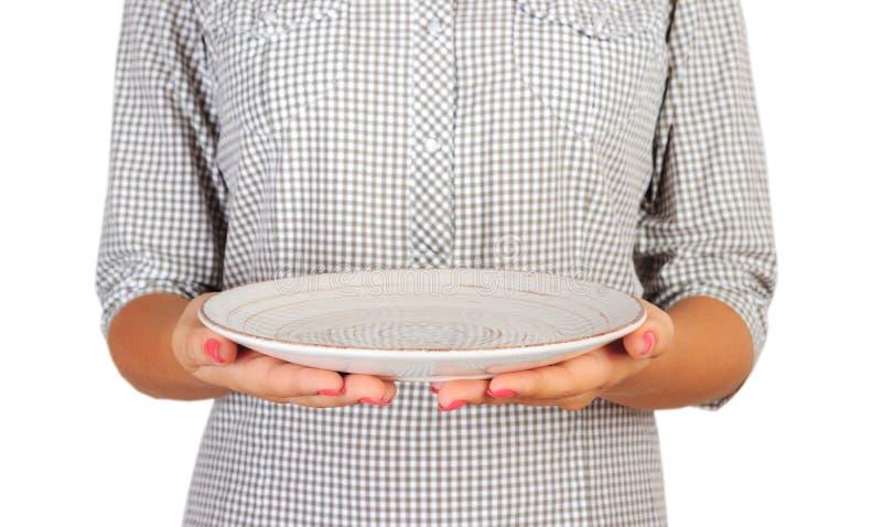 Het meisje in het plaidoverhemd houdt een lege ronde witte plaat voor haar de greep lege schotel van de vrouwenhand voor u die de stock afbeelding