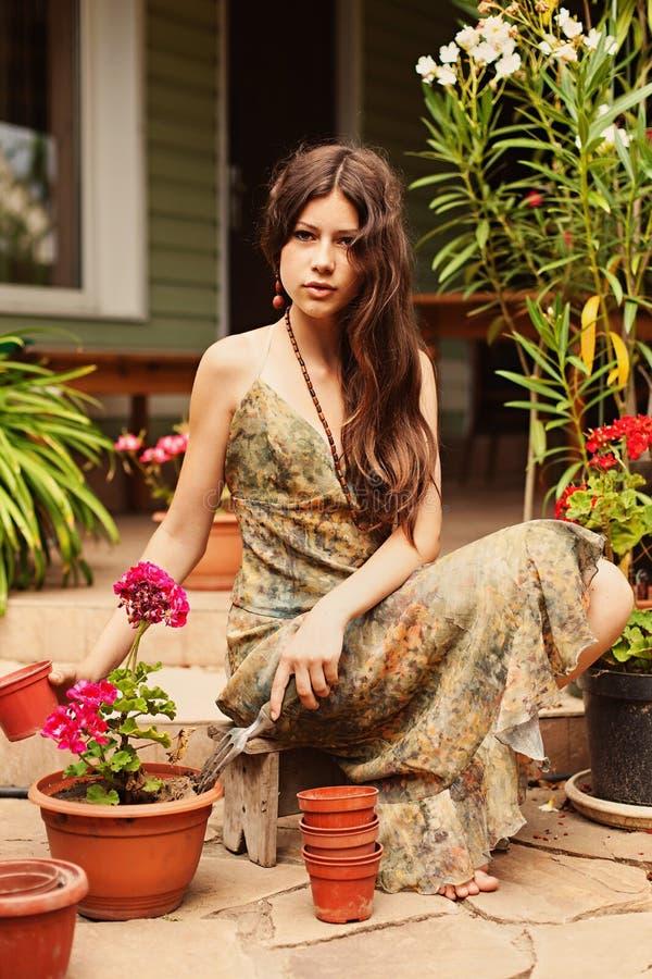 Het meisje plant geraniums in potten over stock foto's
