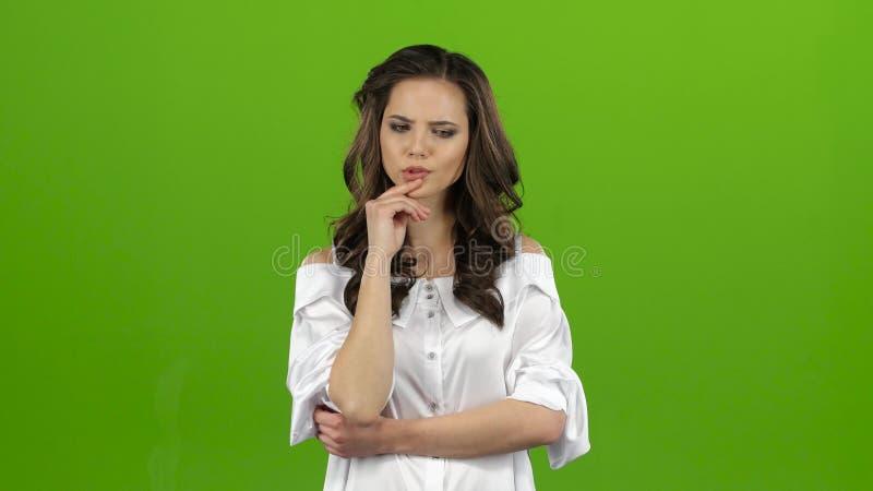 Het meisje probeert om het antwoord aan de vraag te vinden, denkt lange tijd en vindt het antwoord Het groene scherm stock footage