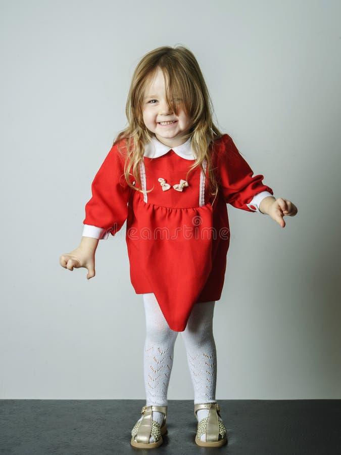 Het meisje in rode kleding maakt fotograaf bang royalty-vrije stock afbeelding