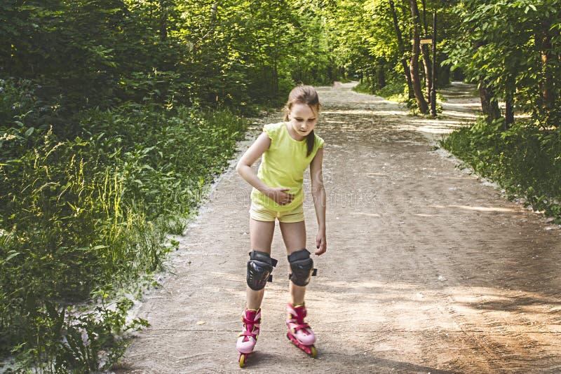 Het meisje rolt op de rollen in het park royalty-vrije stock afbeelding
