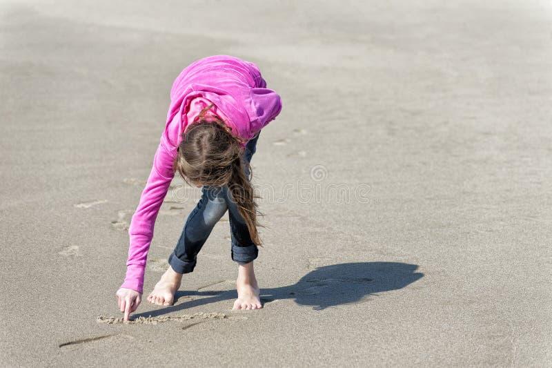 Het meisje in roze sweatshirt trekt in zand op strand royalty-vrije stock afbeelding