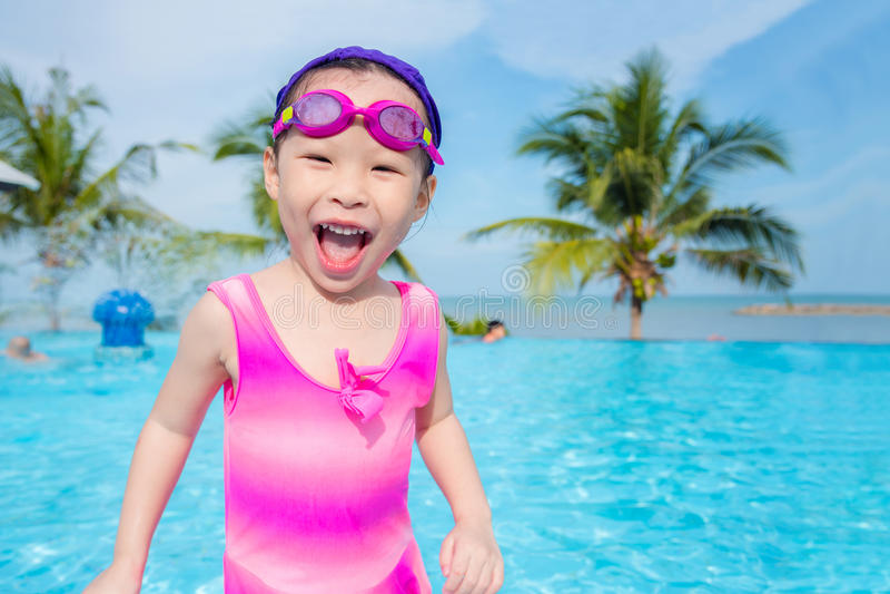 Het meisje in roze zwemt kostuum glimlachend in zwembad stock fotografie