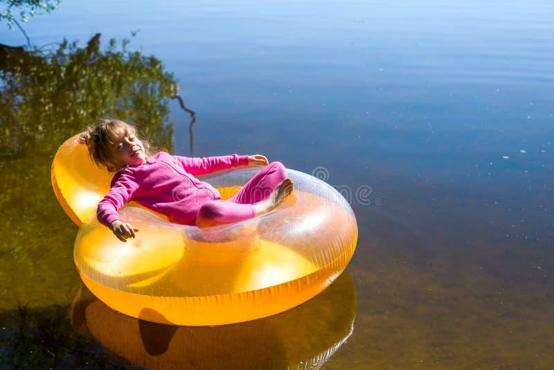 Het meisje rust als opblaasbare voorzitter, die op het water drijven royalty-vrije stock afbeelding