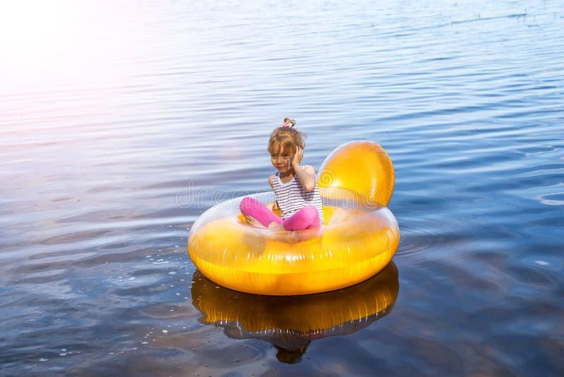 Het meisje rust als opblaasbare voorzitter op het water Het kind spreekt op smartphone stock foto's