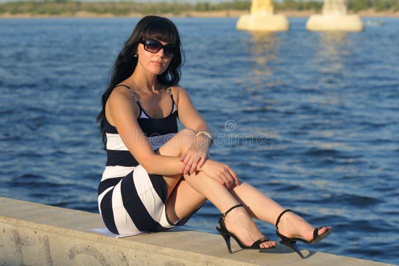 Het meisje rust dichtbij het water stock afbeeldingen