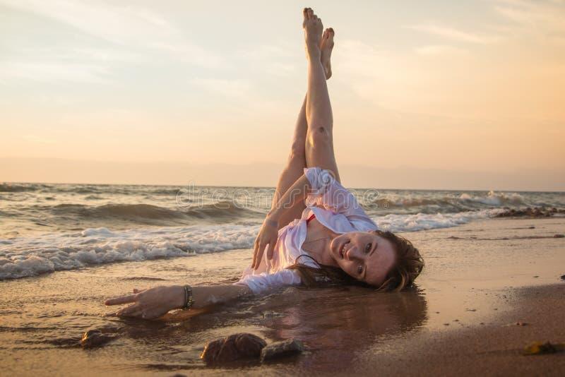 Het meisje rust en heeft pret in overzeese golf bij zonsondergang royalty-vrije stock foto
