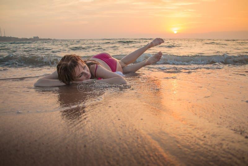 Het meisje rust en heeft pret in overzeese golf bij zonsondergang royalty-vrije stock fotografie
