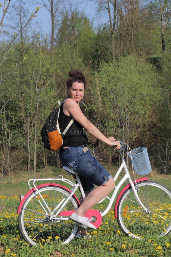 Het meisje rust op de de lenteweide Zit op een fiets, achter een toeristenrugzak De paardebloemen zijn bloeiend, is het jonge gra stock afbeeldingen
