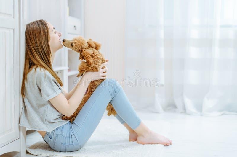 Het meisje rust thuis met een hond op de vloer stock foto