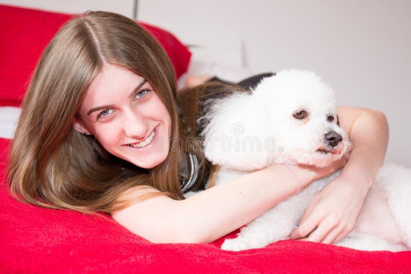 Het meisje rust thuis op bed met poedelhond op bed stock afbeelding