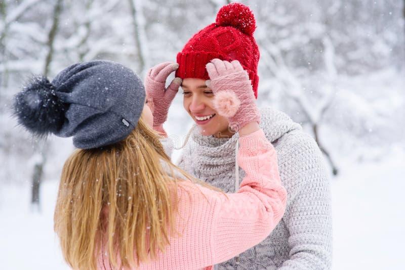 Het meisje schikt hoed van haar geliefde vriend stock afbeelding