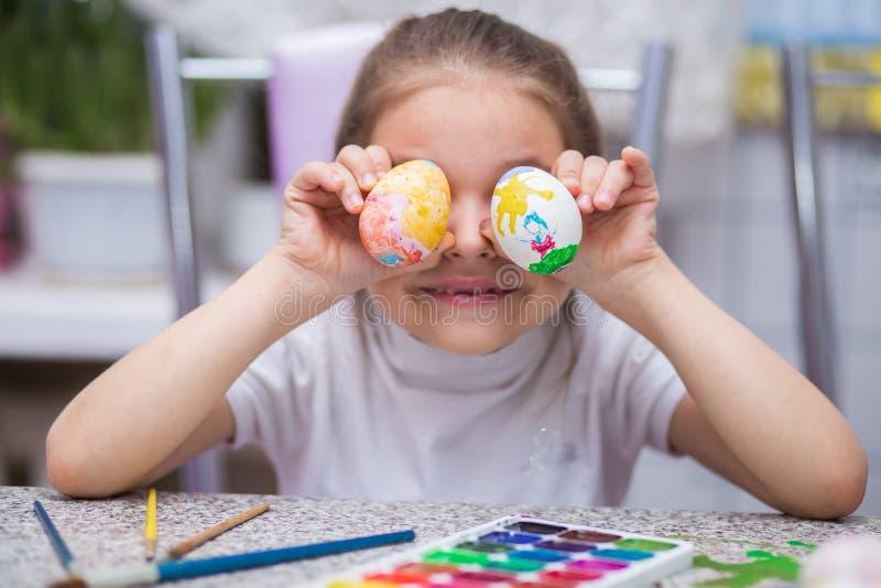 Het meisje schilderde paaseieren met waterverfverven en houdt hen dichtbij ogen en lacht kinderen` s vermaak royalty-vrije stock afbeelding