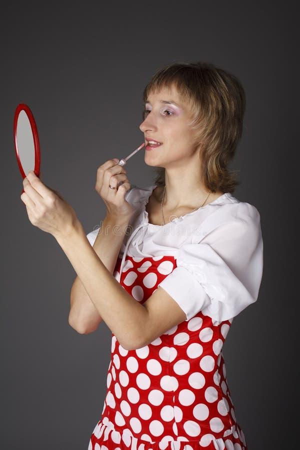 Het meisje schildert lippen stock foto