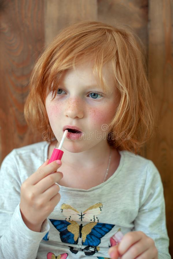 Het meisje schildert lippen met schittering royalty-vrije stock fotografie