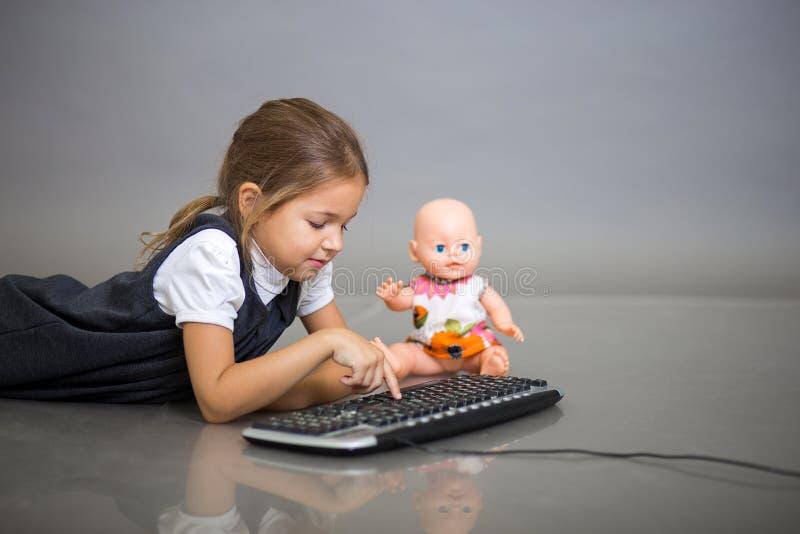 Het meisje het schoolmeisje op een grijze achtergrond speelt met het toetsenbord van de computer en een pop royalty-vrije stock fotografie
