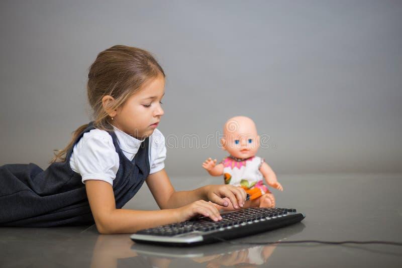 Het meisje het schoolmeisje op een grijze achtergrond speelt met het toetsenbord van de computer en een pop royalty-vrije stock afbeeldingen