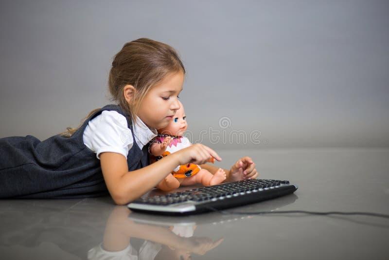 Het meisje het schoolmeisje op een grijze achtergrond speelt met het toetsenbord van de computer en een pop stock fotografie