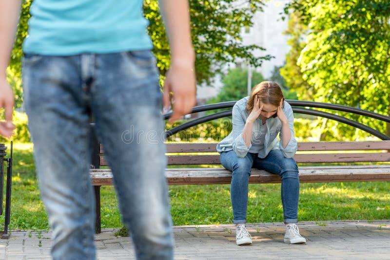 Het meisje schreeuwt op bank In de zomer in het park in aard De jonge man verlaat haar De frustratie is een wantrouwen stock foto's