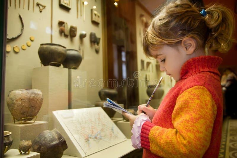 Het meisje schrijft aan schrijven-boeken bij excursie royalty-vrije stock foto's