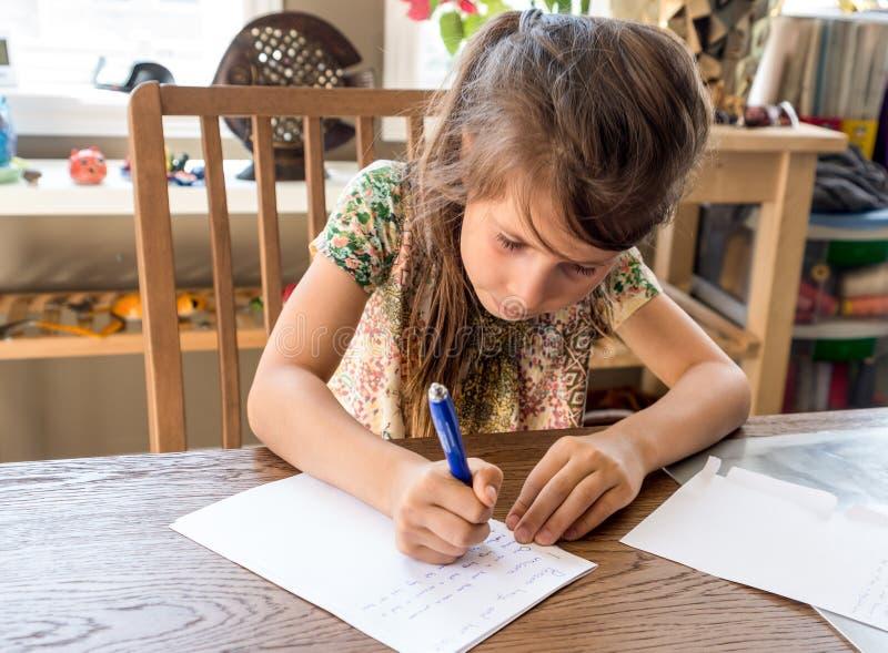 Het meisje schrijft haar thuiswerk stock fotografie