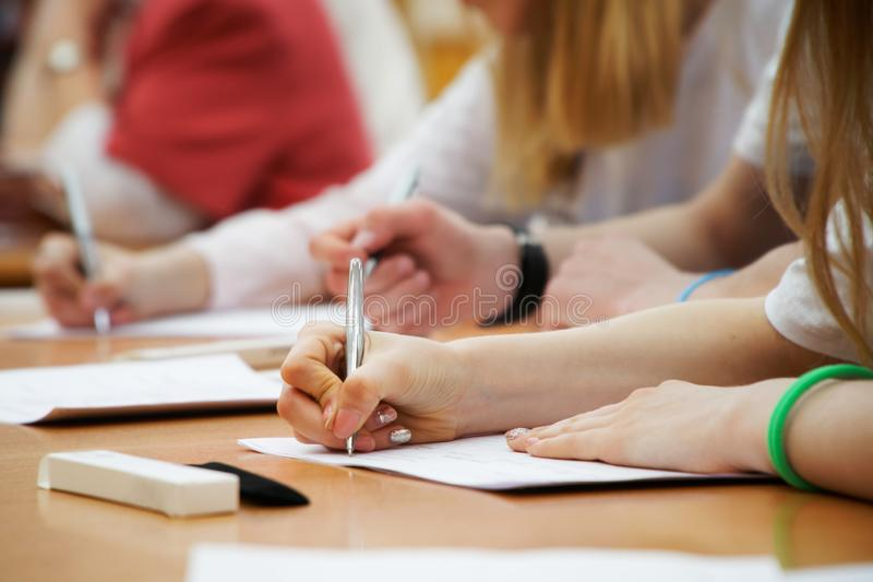 Het meisje schrijft met een vulpen op een stuk van document tijdens klassen bij school of universiteit Onderzoek, examens stock fotografie