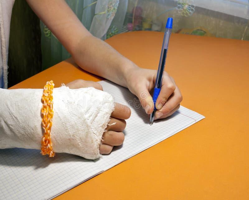 Het meisje schrijft met zijn linkerhand stock afbeeldingen