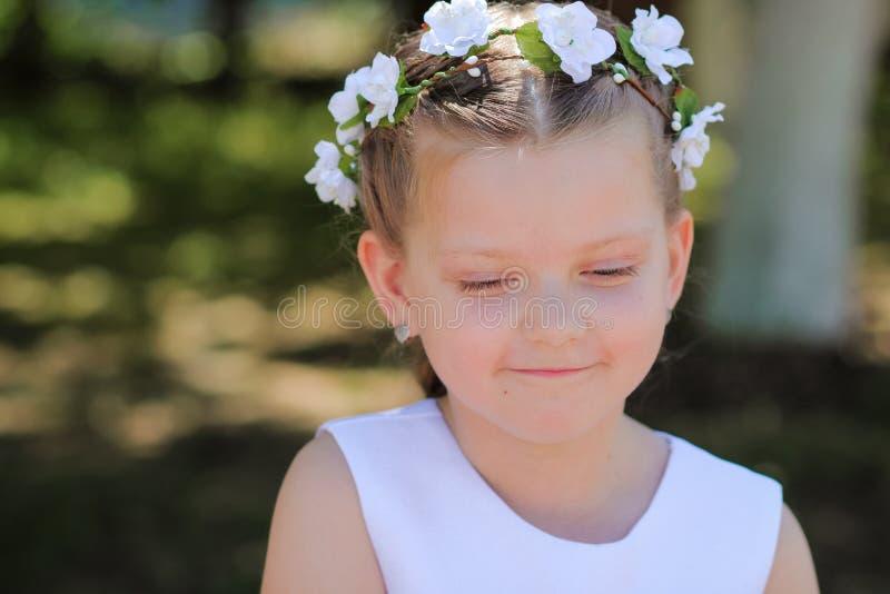 Het meisje is schuw en kijkt neer, een kind met een kroon van kunstbloemen op haar hoofd royalty-vrije stock foto's