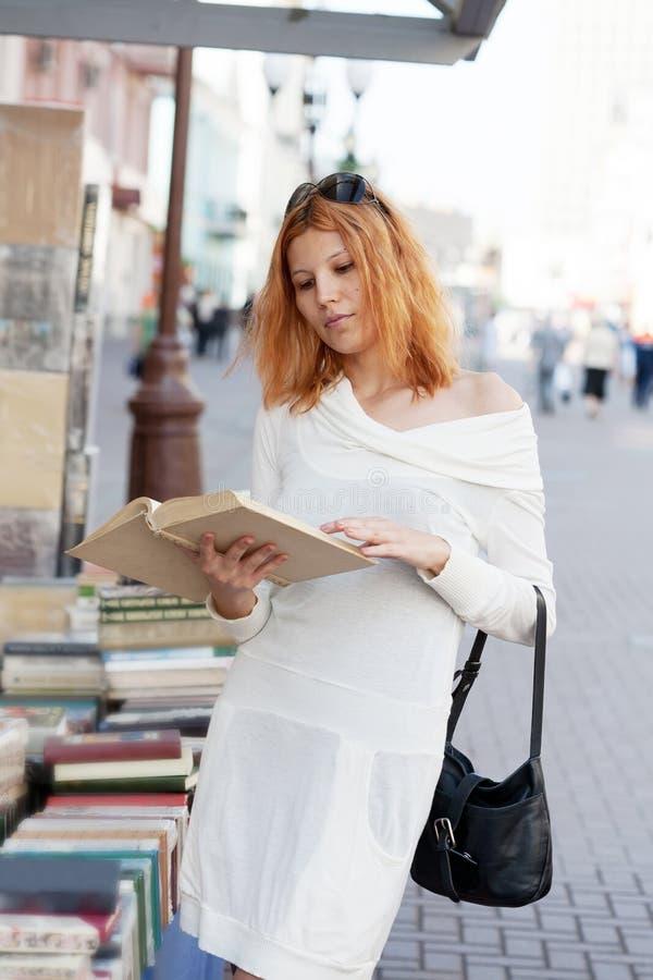 Het meisje selecteert het boek royalty-vrije stock afbeeldingen