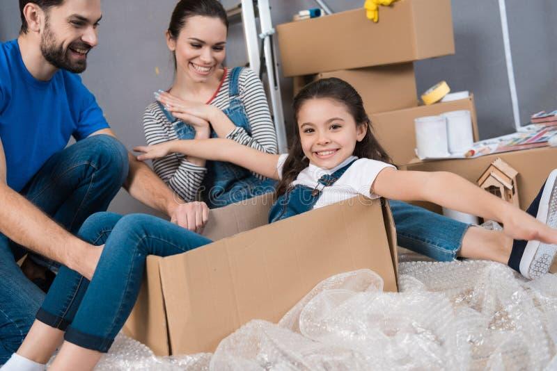 Het meisje simuleert vlucht op vliegtuig, zittend in doos naast ouders Huisvernieuwing voor verkoop royalty-vrije stock foto's