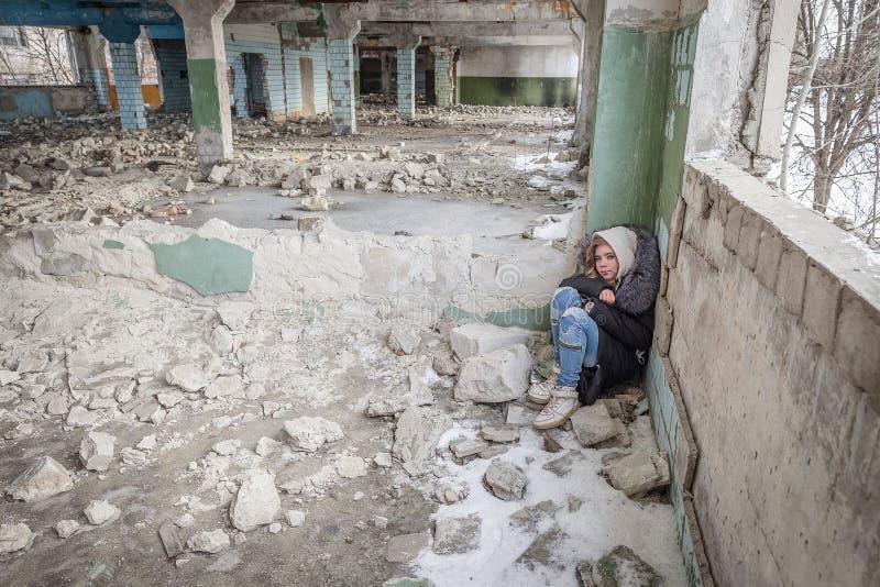 Het meisje slaapt in een geruïneerd gebouw stock foto