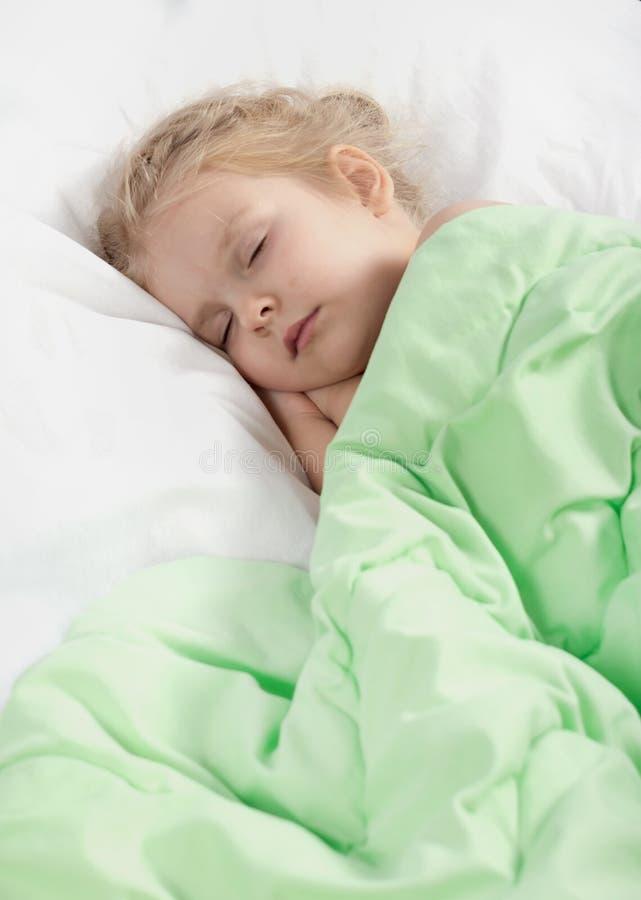 Het meisje slaapt met een deken Een leuk blond kind rust in bed Close-up royalty-vrije stock afbeeldingen