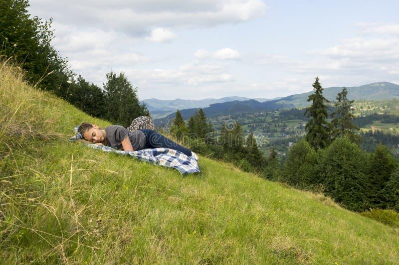 Het meisje slaapt op een berghelling royalty-vrije stock foto's