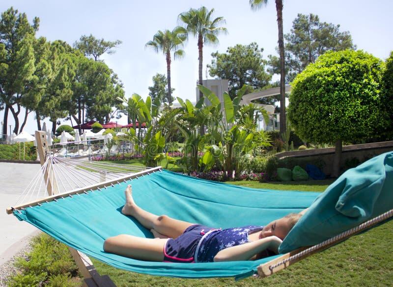 Het meisje slaapt op een turkooise hangmat onder een heldere zon op a royalty-vrije stock foto