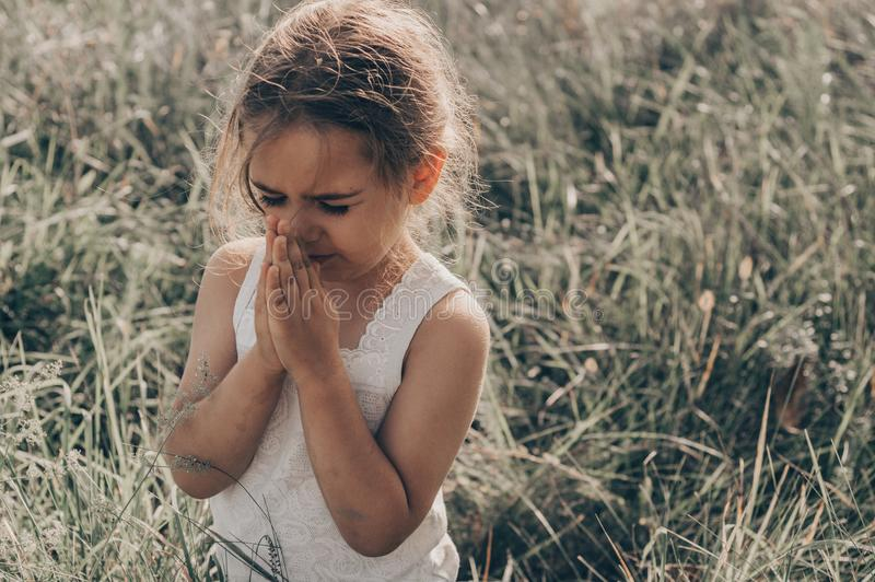 Het meisje sloot haar ogen biddend bij zonsondergang Handen in gebedconcept worden gevouwen voor geloof, spiritualiteit en godsdi stock fotografie